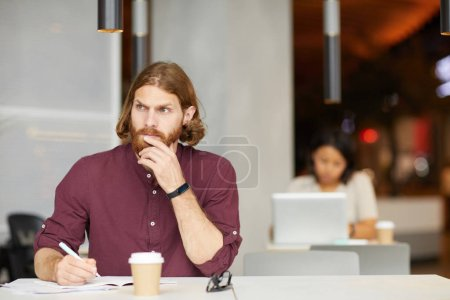 Photo for Red haired bearded businessman sitting at the table making notes and looking pensively with woman in the background in cafe - Royalty Free Image