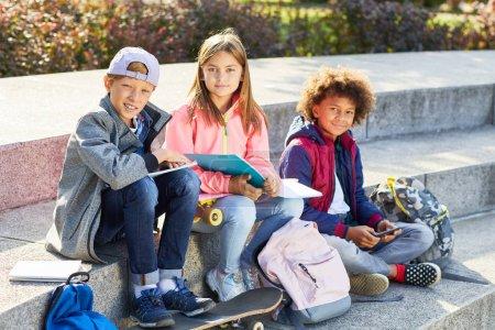 Photo pour Portrait d'un groupe d'écoliers assis dans des escaliers avec des livres et des sacs à dos et souriant à la caméra à l'extérieur - image libre de droit