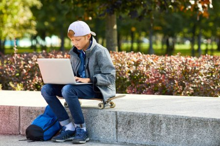Photo for Boy in casual clothing sitting on skateboard and typing on laptop computer outdoors preparing for the homework - Royalty Free Image