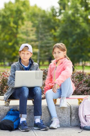 Photo for Portrait of boy and girl sitting on skateboards and looking at camera while using laptop computer outdoors in the park - Royalty Free Image