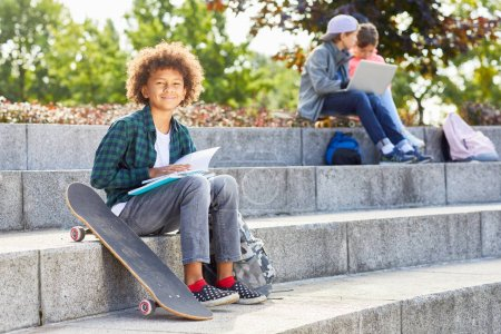 Photo for Portrait of African boy with curly hair sitting on stairs with skateboard and smiling at camera while reading book with children in the background - Royalty Free Image