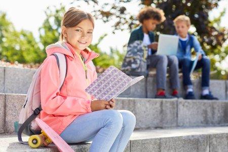 Photo pour Portrait d'écolière avec sac à dos souriant à la caméra tout en étant assis sur les escaliers à l'extérieur et en lisant le livre - image libre de droit