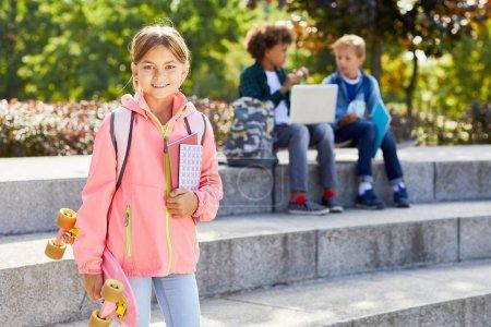 Photo pour Portrait d'écolière tenant skateboard et livres souriant à la caméra tout en se tenant debout à l'extérieur avec des amis en arrière-plan - image libre de droit