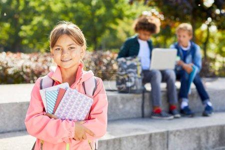 Photo pour Portrait d'écolière mignonne tenant des livres et souriant à la caméra tout en se tenant dans le parc avec des camarades de classe en arrière-plan - image libre de droit