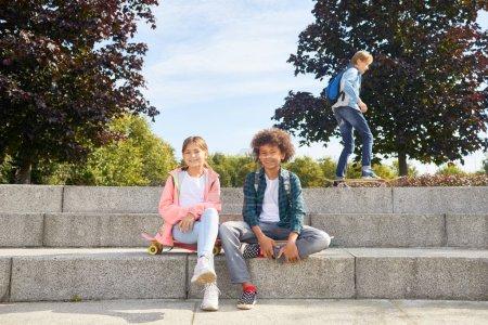 Photo pour Portrait de petite fille avec un garçon africain assis sur les escaliers et se reposant après le skateboard dans le parc - image libre de droit