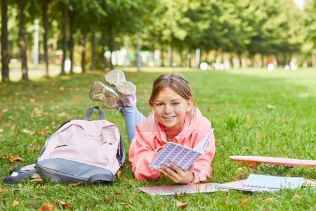 Photo pour Portrait d'écolière mignonne allongée sur de l'herbe verte avec sac à dos et livres et lecture avant les cours à l'école - image libre de droit
