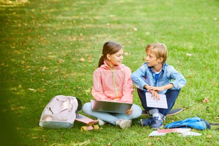 Photo for Schoolgirl sitting on green grass with laptop and talking to friend preparing for the lessons together before school - Royalty Free Image