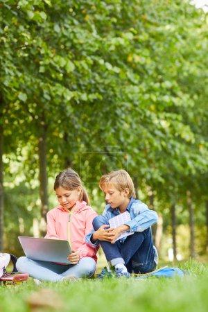 Photo pour Fille en utilisant un ordinateur portable avec son camarade de classe tout en étant assis sur l'herbe verte à l'extérieur - image libre de droit