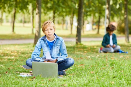 Photo for Portrait of boy in casual clothing sitting on green grass with laptop computer and looking at camera - Royalty Free Image