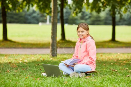Photo for Portrait of cute schoolgirl sitting on green grass and smiling at camera while reading textbook and using laptop - Royalty Free Image