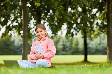 Photo for Portrait of cute girl sitting on green grass with book and smiling at camera while using laptop computer outdoors - Royalty Free Image