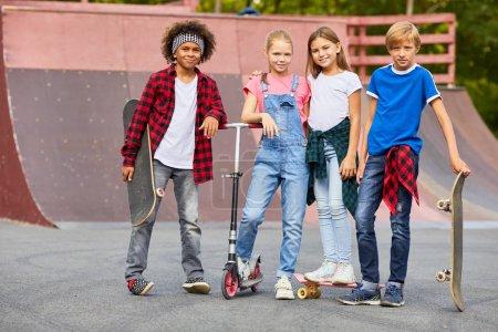 Photo pour Groupe d'enfants multiethniques debout avec des planches à roulettes et regardant la caméra au parc de planche à roulettes - image libre de droit