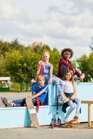Foto de Retrato de niños sonriendo a la cámara mientras están sentados en el banco y descansando después de montar en monopatines en el parque - Imagen libre de derechos