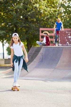 Photo pour Fille apprendre à monter sur skateboard au parc de skateboard avec des enfants en arrière-plan - image libre de droit