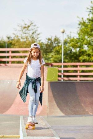 Foto de Chica en ropa casual de pie en el monopatín y aprender a montar en el parque de skate al aire libre - Imagen libre de derechos