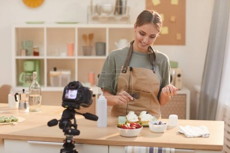 Photo for Young woman decorating cakes with berries while standing at the kitchen table and showing it to the camera for her blog - Royalty Free Image