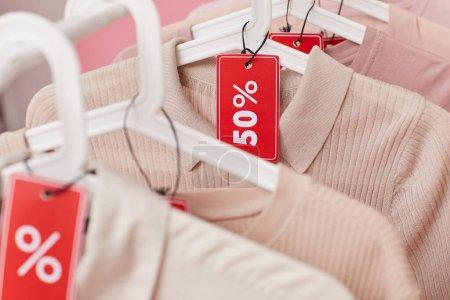 Photo pour Gros plan sur les vêtements suspendus sur le rack avec vente - image libre de droit
