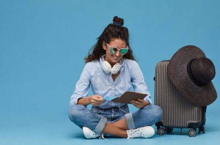 Photo for Young woman in sunglasses sitting on the floor near the luggage and using digital tablet she ordering tickets online - Royalty Free Image