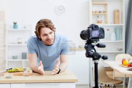 Photo for Young man shooting the video he telling about the healthy food to his followers while standing in the kitchen - Royalty Free Image