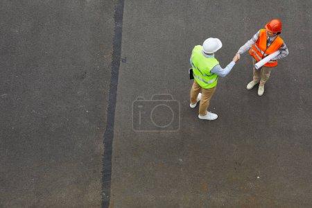 Photo pour Vue grand angle de deux ingénieurs en gilets réfléchissants et en casques de travail serrant la main pendant qu'ils se tiennent debout à l'extérieur - image libre de droit
