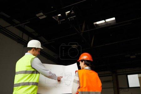 Photo pour Vue arrière de deux ingénieurs en gilets réfléchissants regardant le plan et discutant du projet de nouvelle construction en équipe - image libre de droit
