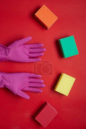 Photo pour Vue grand angle des gants en caoutchouc et des éponges colorées isolées sur fond rouge - image libre de droit