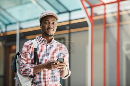 Photo for African young man in cap with backpack behind his back smiling at camera while using his mobile phone - Royalty Free Image