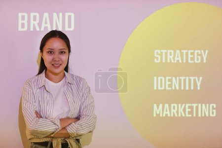 Photo for Portrait of smiling confident young Asian brand manager with crossed arms standing against projection screen with marketing thesis - Royalty Free Image