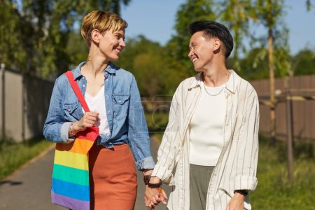 Photo pour Deux lesbiennes heureuses qui se sourient et se parlent tout en marchant dans la rue - image libre de droit