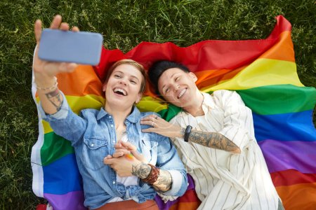Photo for High angle view of two lesbians lying on colored flag and making selfie portrait on mobile phone outdoors - Royalty Free Image
