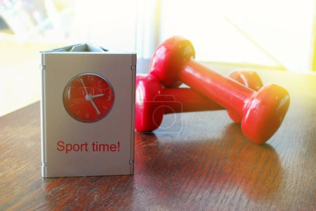Photo for Alarm clock and red sports dumbbells on a brown table - Royalty Free Image