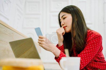 Photo pour Belle asiatique thai longue femme aux cheveux foncés en chemise rouge liste de vérification sur papier collant note avant de travailler sur ordinateur portable. - image libre de droit