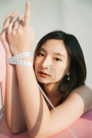 Photo for Fashion portrait - Beautiful asian thai woman tie her hands with measure tape. - Royalty Free Image