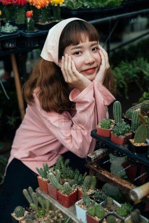 Photo pour Brunette fille en bandeau beige et rose t-shirt à manches longues assis dans la serre parmi le lit de fleurs de bébé plante - image libre de droit
