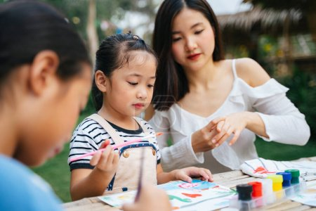 Photo for Asian big sister helping little sister painting water colour on paper outdoors. - Royalty Free Image