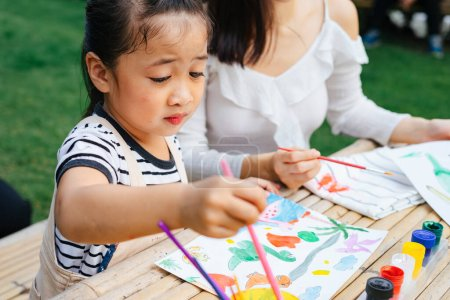 Photo for Close up asian little girl painting water colour with brush on paper outdoors. - Royalty Free Image