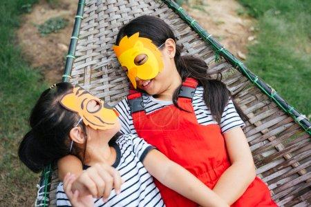 Photo pour Joyeux asiatique petites filles portant dessin animé animal masque pose sur un lit de camp en regardant l'autre visage. - image libre de droit