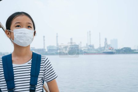 Photo for Virus protection concept - asian little girl wearing protective mask, standing near river in smog day. Pollution every where. - Royalty Free Image