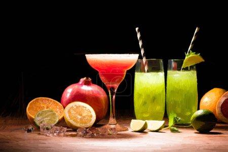 Photo pour Boissons d'alcool rouges et vertes peintes dans des verres à cocktail près de fruits sur noir - image libre de droit