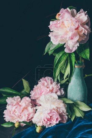 painted light pink blooming peonies near vase on black