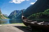 "Постер, картина, фотообои ""painted wooden boat near sea, green trees and mountains """