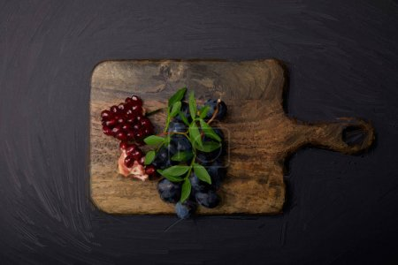Photo for Top view of painted cutting board with grapes and pomegranate seeds on black - Royalty Free Image