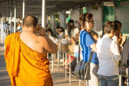 Photo pour Thani, Thaïlande - 3 février 2017 : Moine tatoué marchant parmi la file d'attente des gens, festival Udon . - image libre de droit