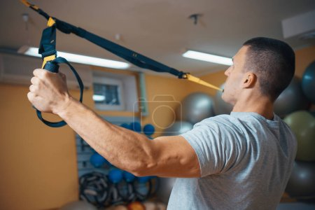 young man is engaged in a gym in the trx