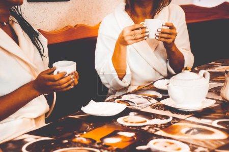 Photo pour Les filles boivent du thé dans le salon de spa - image libre de droit