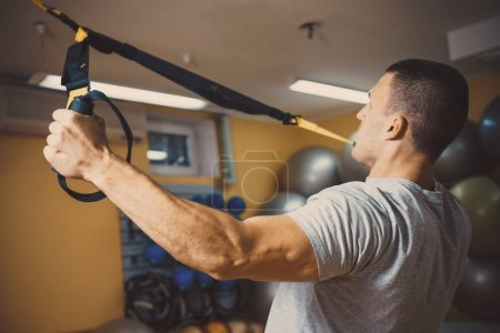 Young man is engaged in a gym in the trx...