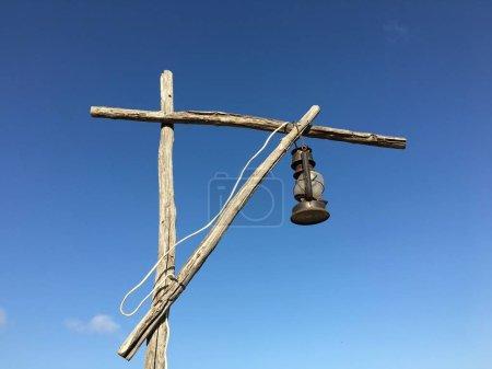 Photo pour Vieille lampe rouillée au kérosène avec un fil blanc sur une grue en bois de rue contre le ciel bleu par temps ensoleillé . - image libre de droit