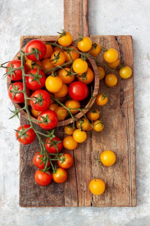Photo for Ripe cherry tomatoes on a wooden board - Royalty Free Image
