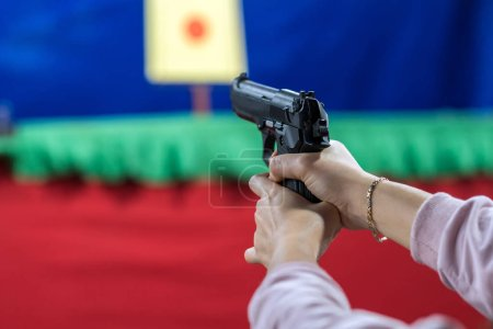 Rear view of woman with her gun on shooting at the target in practice Shooting Range, sport and Soldier concept