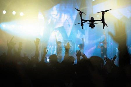 Photo pour Silhouette rapprochée de Drone volant pour prendre la vidéo de la foule de concert et fanclub de musique avec action de la main de spectacle qui suivent le chanteur sur le devant de la scène, concept musical et de concert - image libre de droit